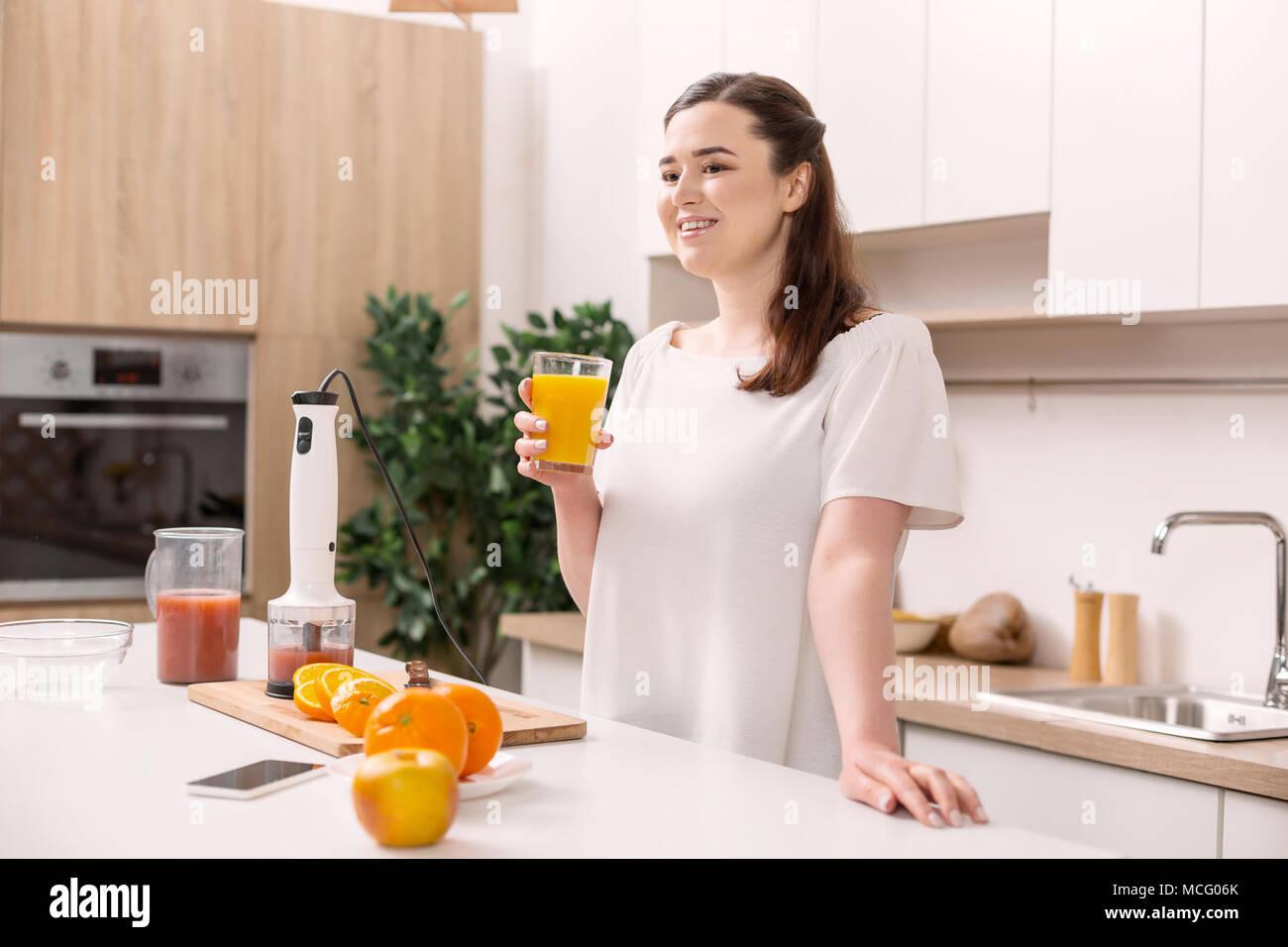 Meditative happy woman drinking orange fresh - Stock Image