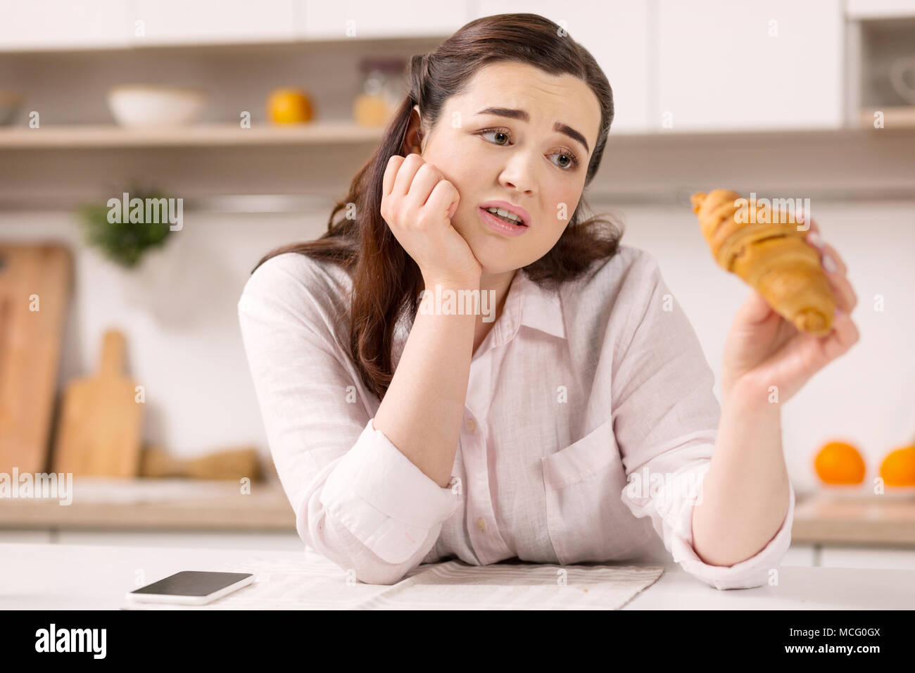 Depressed gloomy woman regretting about croissant - Stock Image