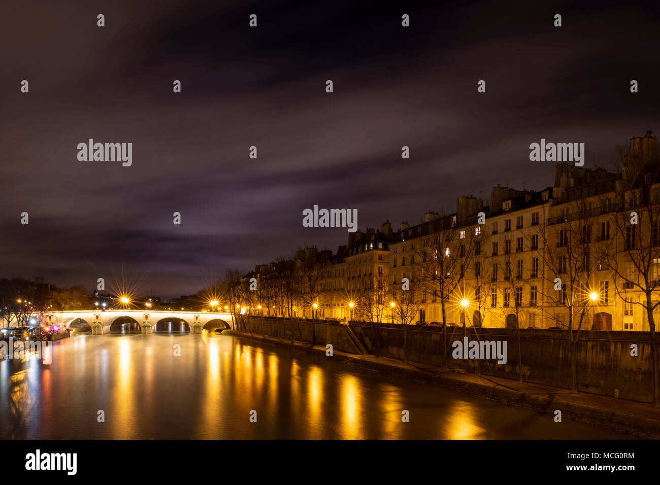 Fast moving clouds over the Seine, Pont Marie and Il St Louis at night. Paris, France, Europe - Stock Image