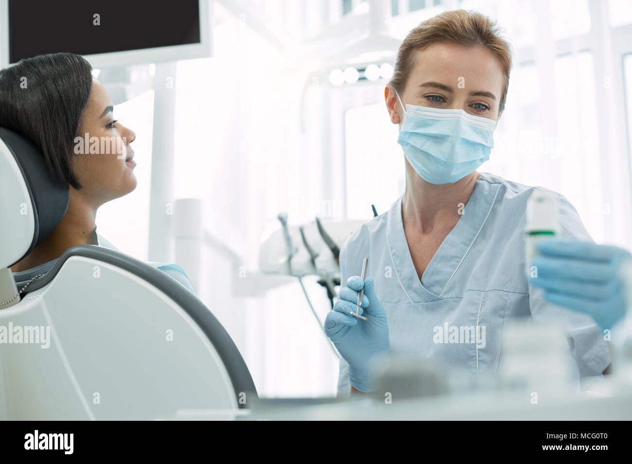 Serious dentist holding an instrument - Stock Image