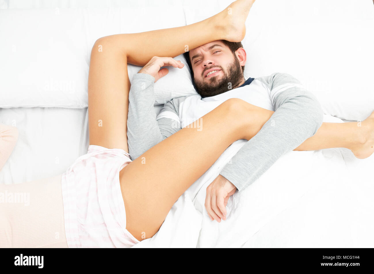 Couple in bed. Insomnia, man can't sleep - Stock Image