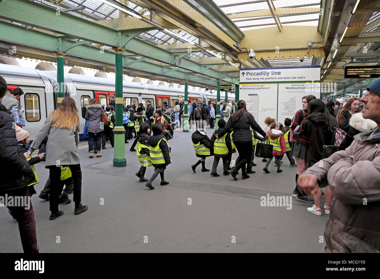 A group of schoolchildren in fluorescent yellow jackets being led by teachers to train on the Piccadilly Line London underground station KATHY DEWITT - Stock Image