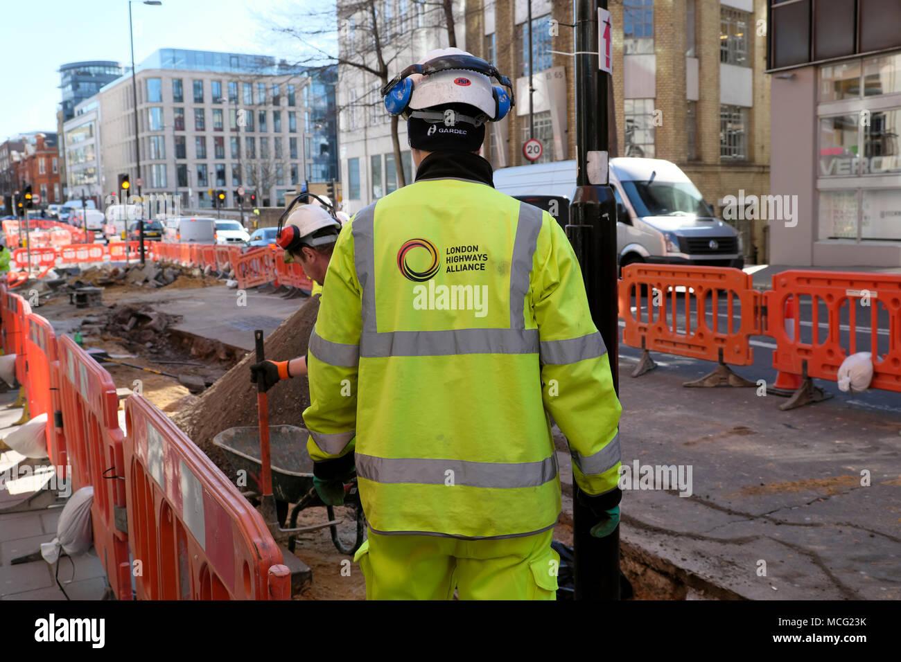 Worker wearing London Highways Alliance logo on back of jacket working on Cycle Superhighway cycling lane on Clerkenwell Road London UK  KATHY DEWITT - Stock Image
