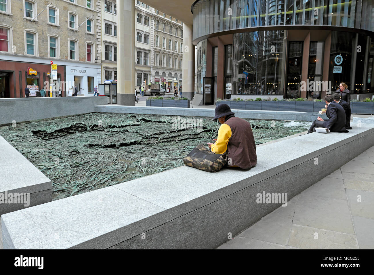 Woman sitting by 'Forgotten Streams' sculpture by artist Cristina Iglesias at the Bloomberg Headquarters building in City of London UK   KATHY DEWITT - Stock Image