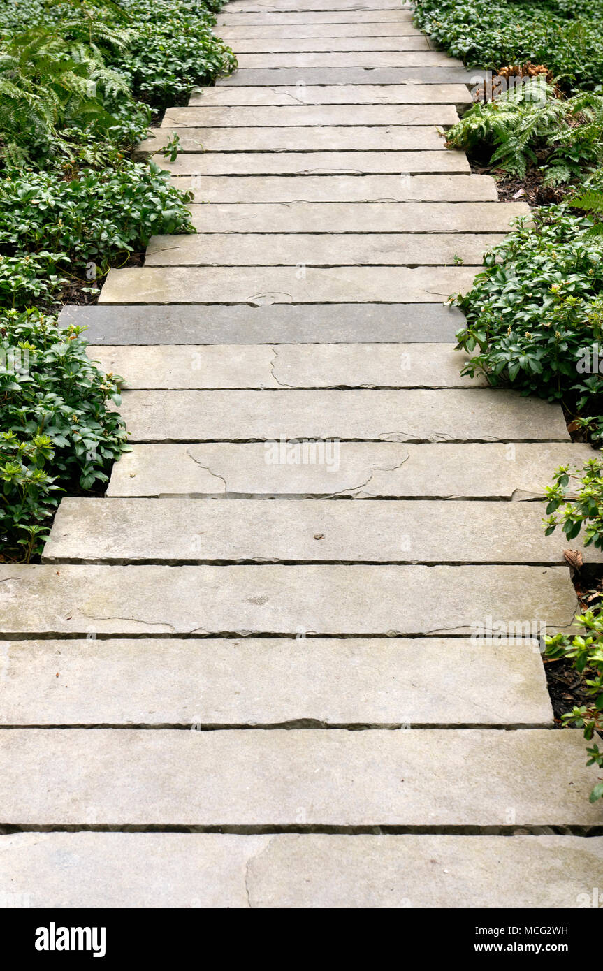 Garden path made of rectangular staggered cement slats - Stock Image
