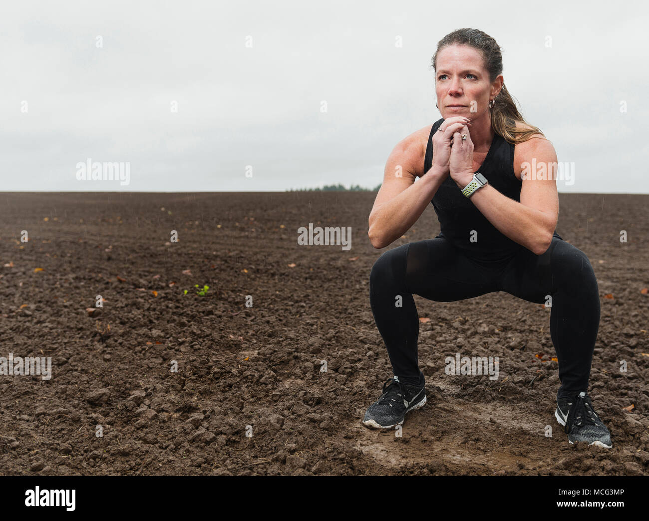 A woman working out in a field during a rain storm. - Stock Image