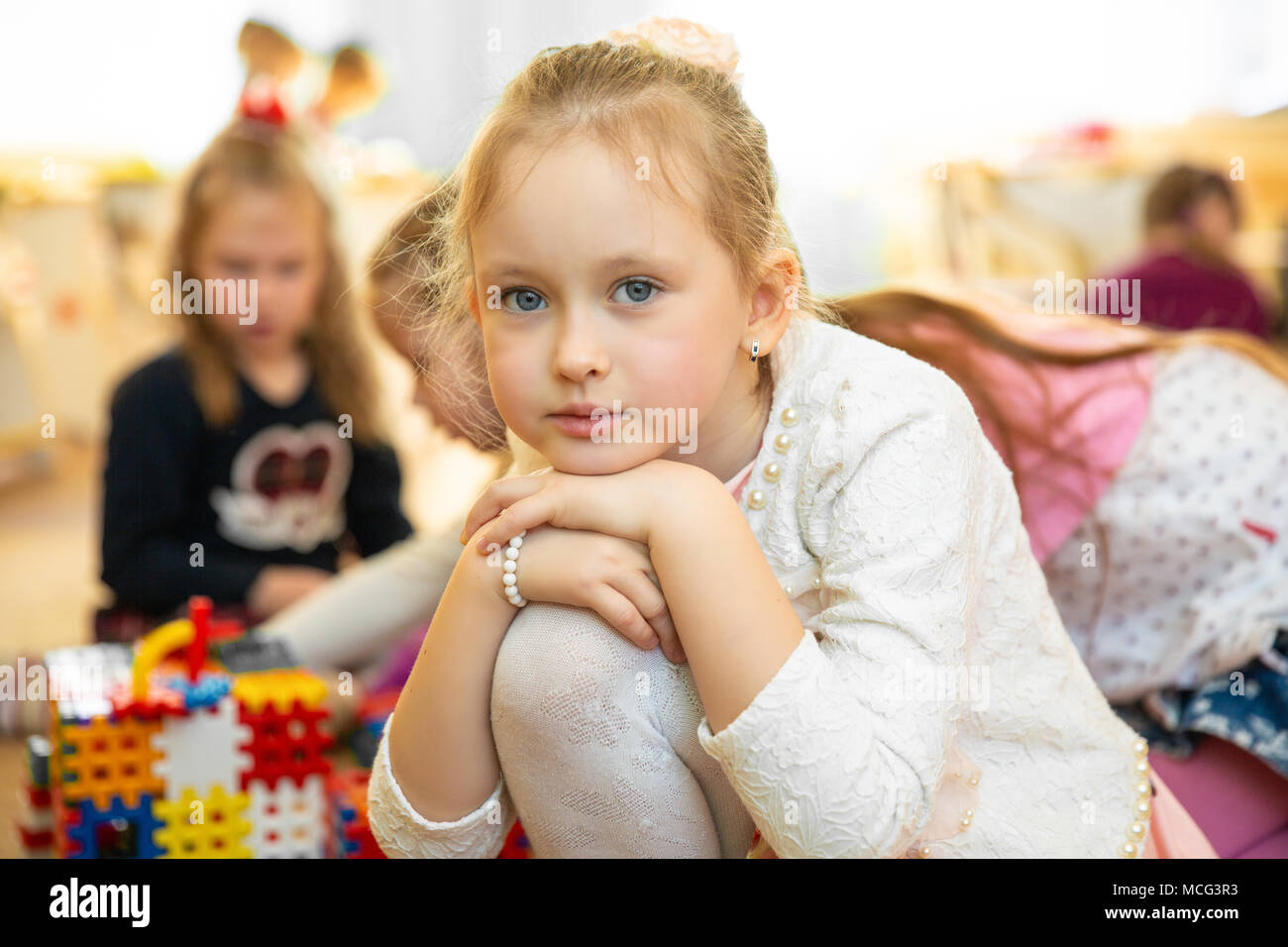 Portrait of sad blond little girl sitting in kindergarten stock image