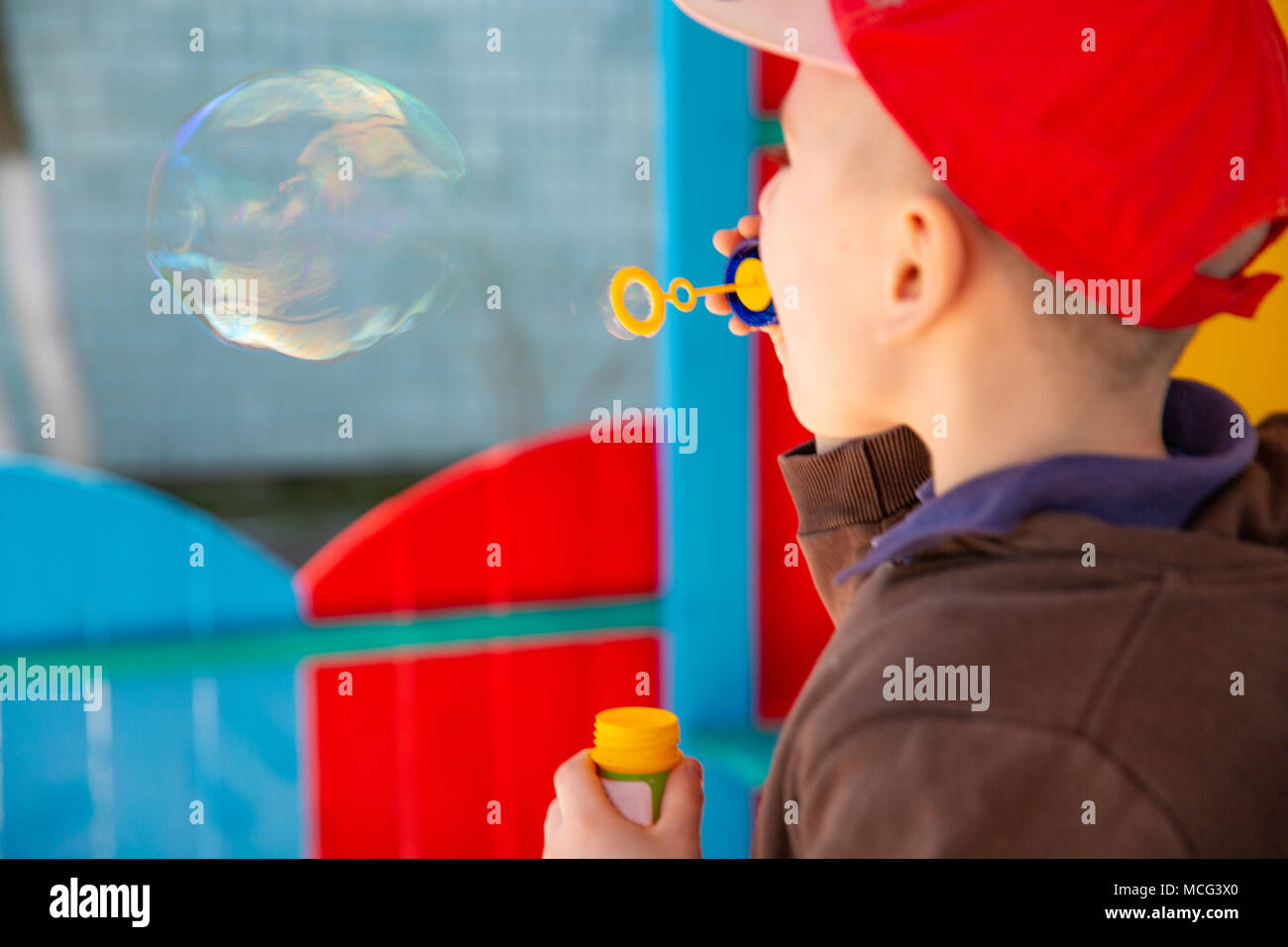 Boy blowing the big soap bubble outdoors. Close up - Stock Image
