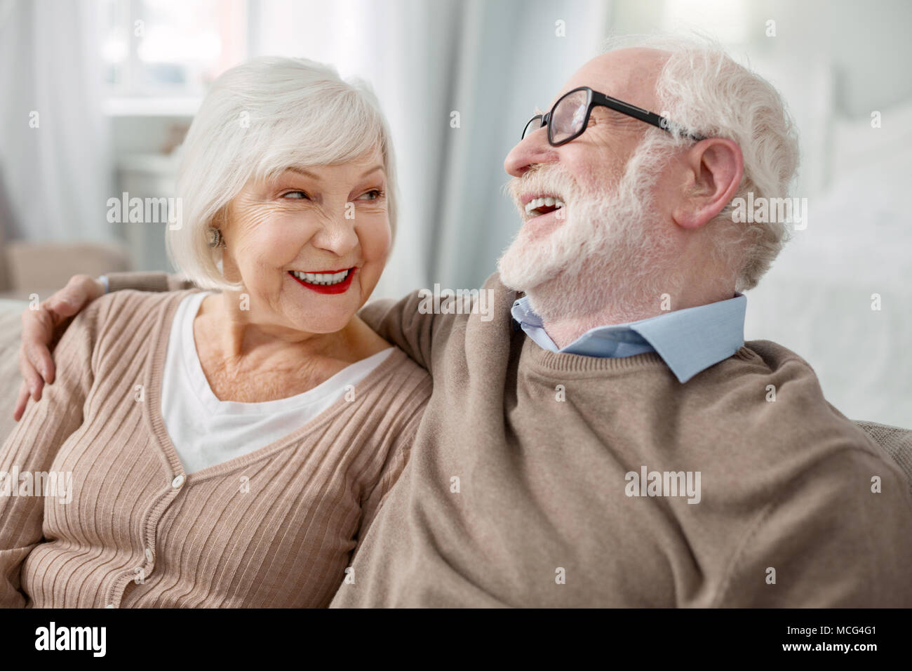 Cheerful elderly man hugging his wife - Stock Image