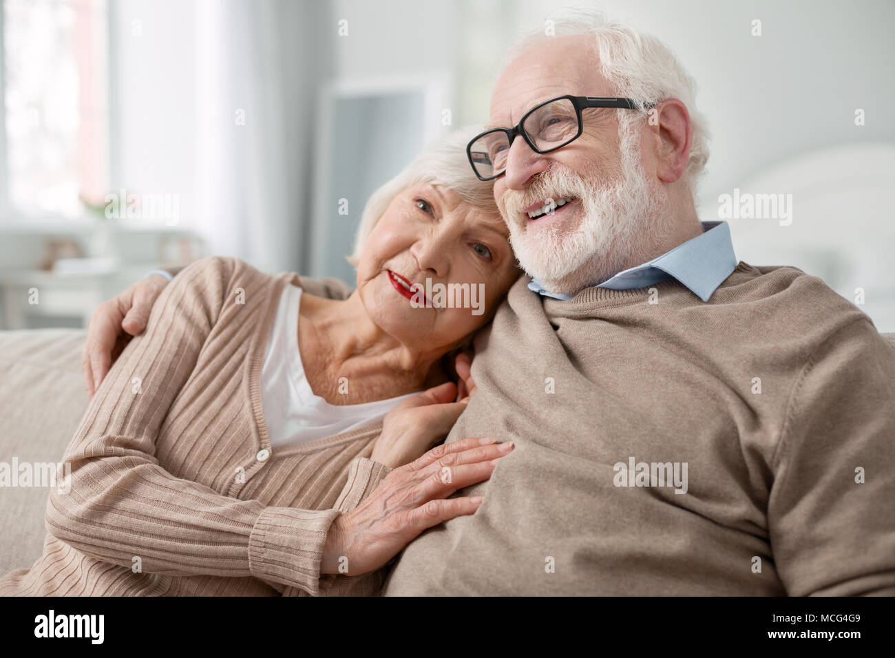 Pleasant aged woman hugging her husband - Stock Image