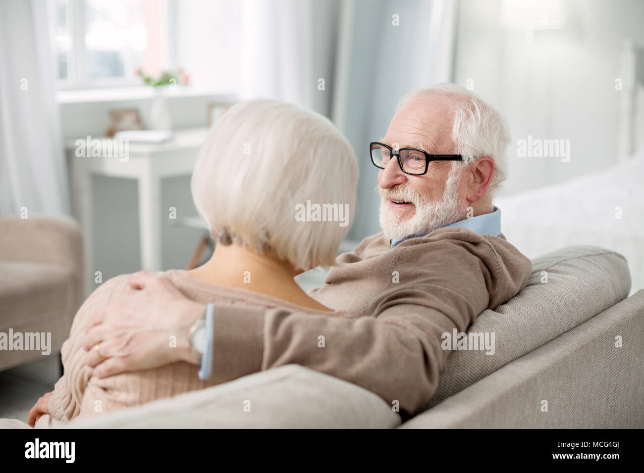 Positive aged couple resting at home - Stock Image