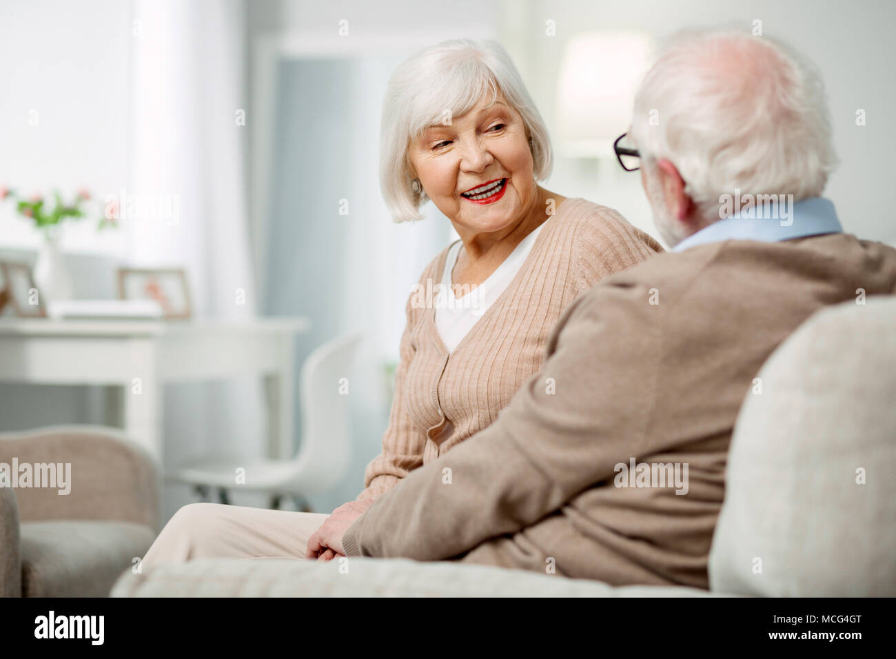 Cheerful aged woman talking to her husband - Stock Image
