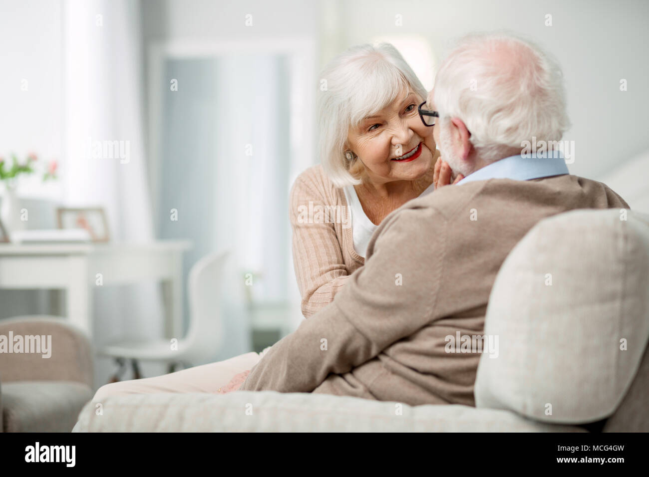 Pleasant elderly woman having a conversation with her husband - Stock Image
