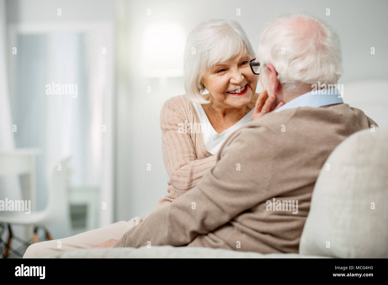 Cheerful senior woman looking at her husbands face - Stock Image
