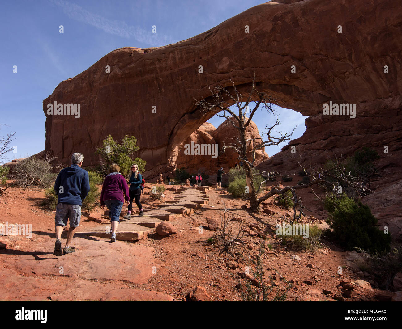 Going West, tourists from around the world, young and old, go to the mountains and wonder the Arches National Park in Moab, Utah. - Stock Image