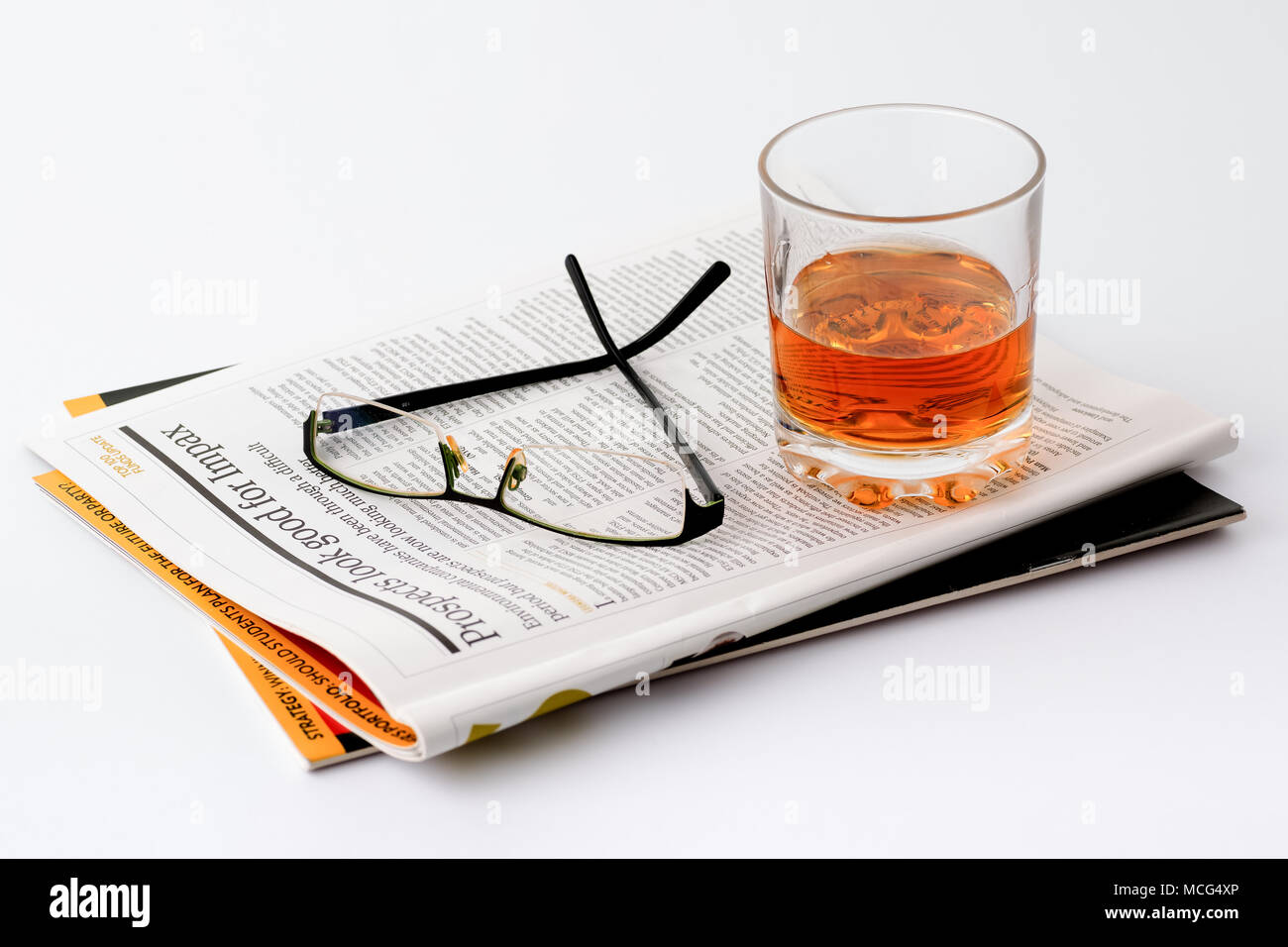 Reading glasses and glass of whiskey on a magazine about Financial Investing, Financial planning, Stock trading. White background. - Stock Image