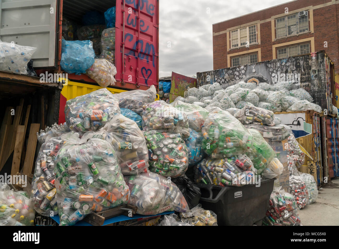 Thousands of bottles and cans await pick-up from distributors at the Sure We Can non-profit redemption center in the Bushwick neighborhood of Brooklyn in New York on Saturday, April 7, 2018. The bags of cans are stored until there are enough to fill a tractor trailer from each individual distributor who is responsible for picking them up. (©ÊRichard B. Levine) - Stock Image