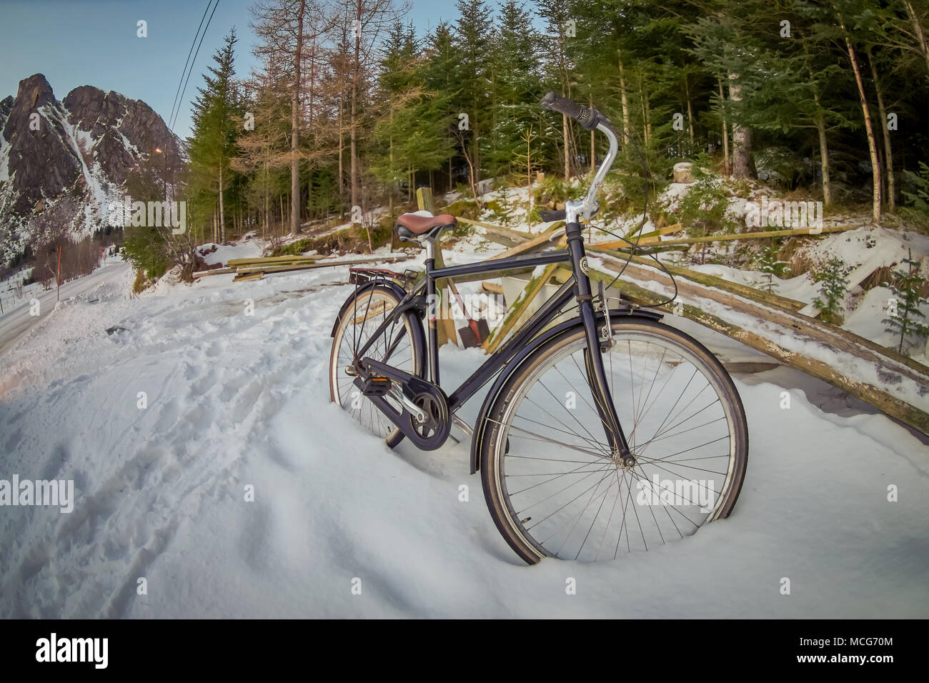 SVOLVAER, LOFOTEN ISLANDS, NORWAY - APRIL 10, 2018: Outdoor view of old-rusty-abandoned bycicles in the snow waiting for the summer to come and be reutilized in Norway - Stock Image