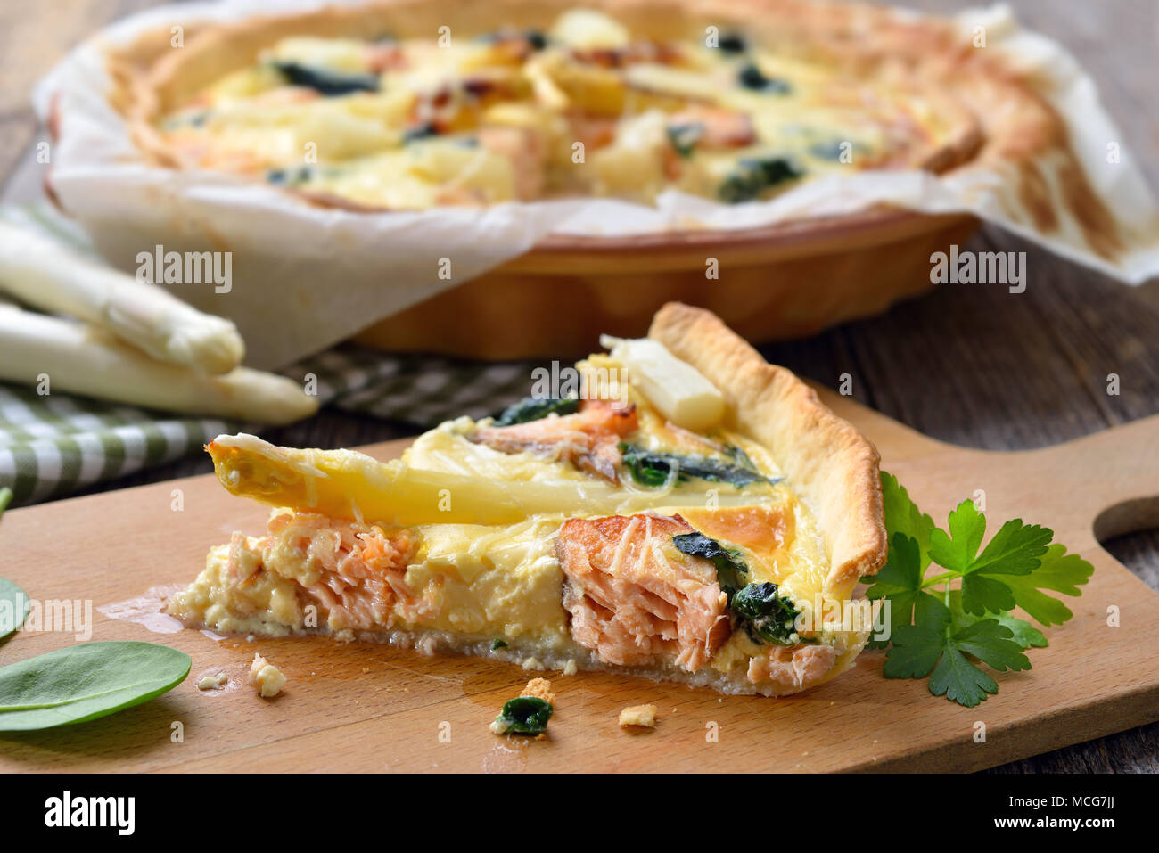 Baked quiche with fresh white asparagus, smoked salmon and spinach - Stock Image