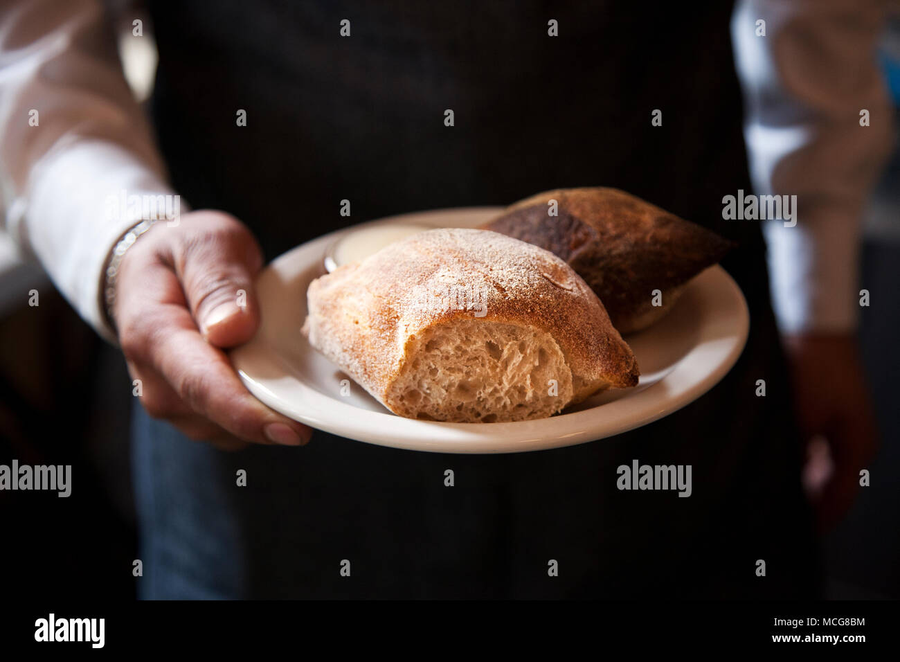 Bread rolls in the hand of a server at Havre 77. Mexico City - Stock Image