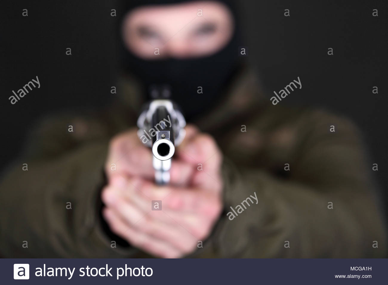 Robber with big revolver threats in front of black background - Stock Image