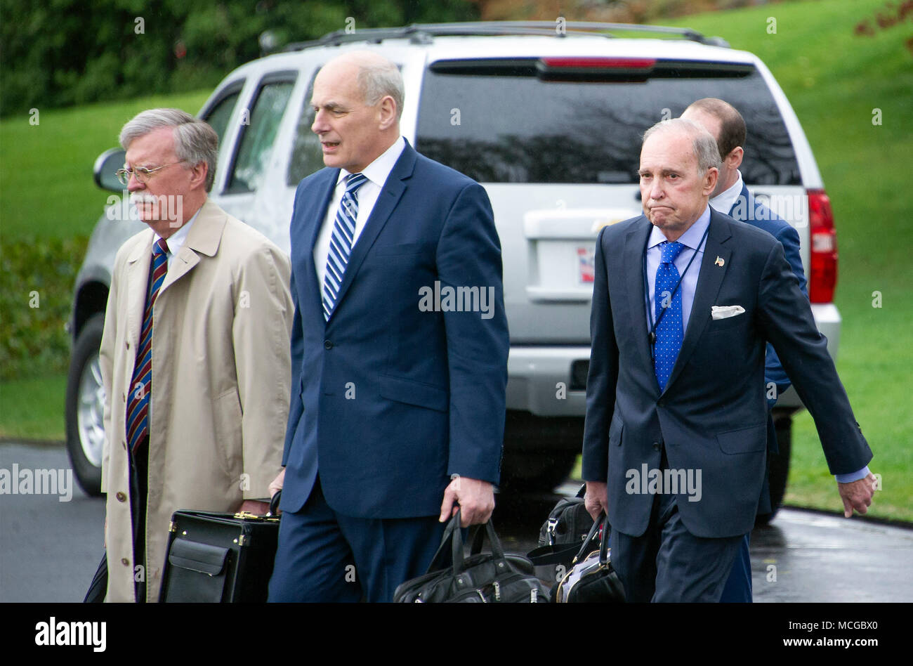 National Security Advisor John Bolton, left, White House Chief of Staff John Kelly, center, and Director of the National Economic Council Larry Kudlow walk across the South Lawn to accompany United States President Donald J. Trump as he departs the White House in Washington, DC on Monday, April 16, 2018. The President is scheduled to go to Mar-a-Lago where he will meet Prime Minister Shinzo Abe of Japan later in the week. Credit: Ron Sachs/CNP /MediaPunch Stock Photo