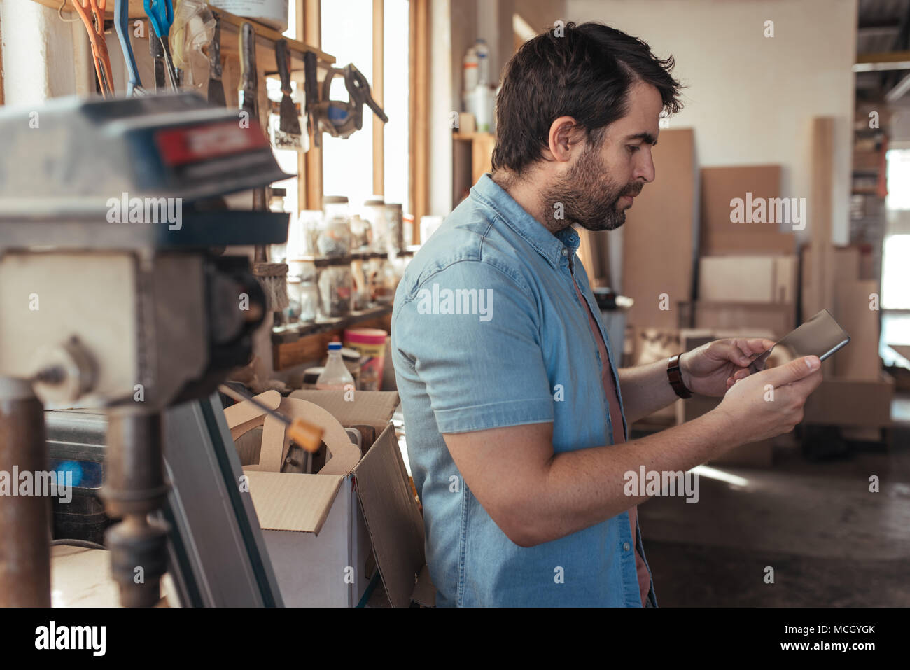 Skilled Young Carpenter Standing At His Workbench Full Of Tools In