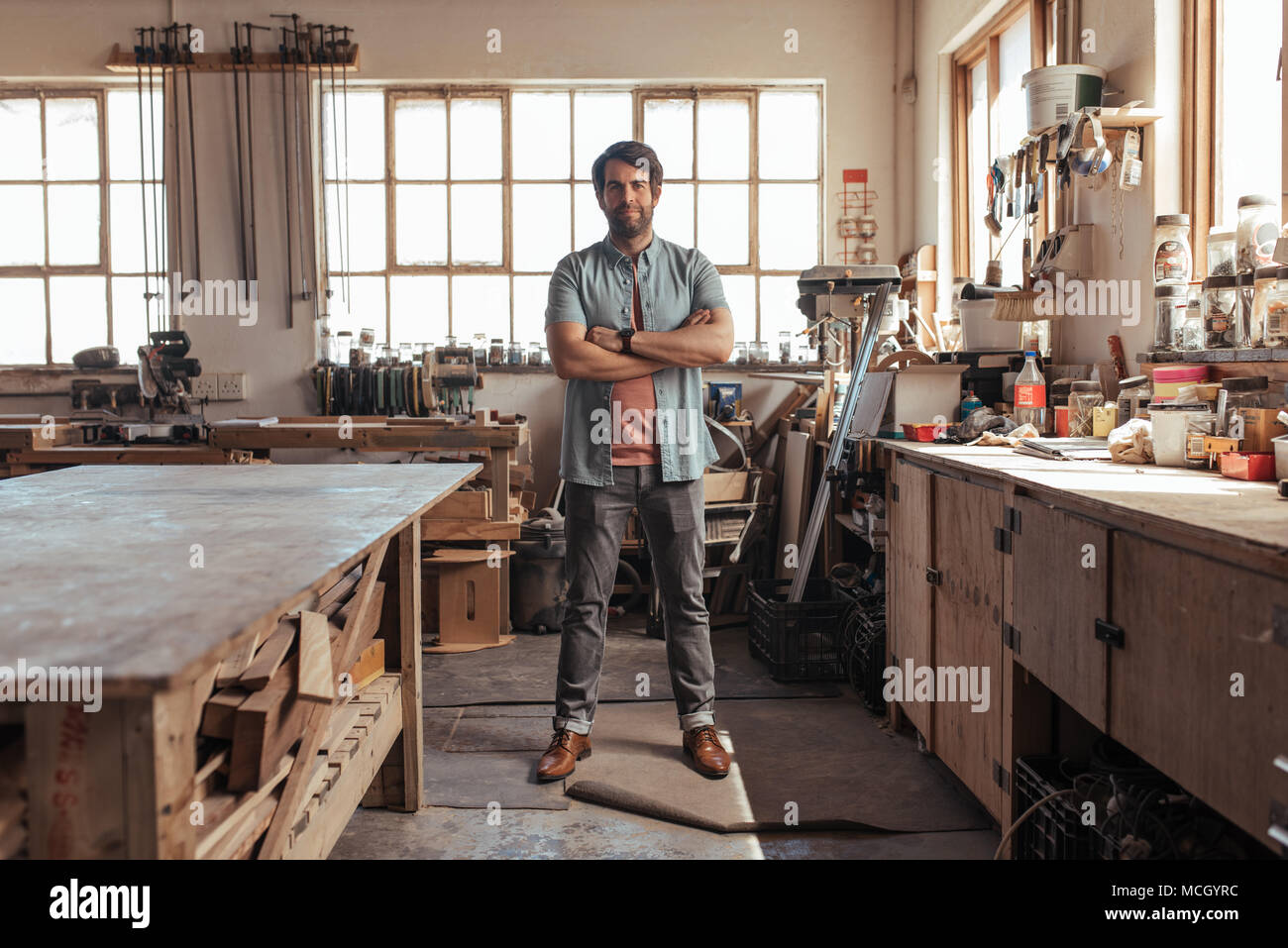 Portrait of a skilled young woodworker standing confidently with his arms crossed in his workshop full of carpentry tools - Stock Image