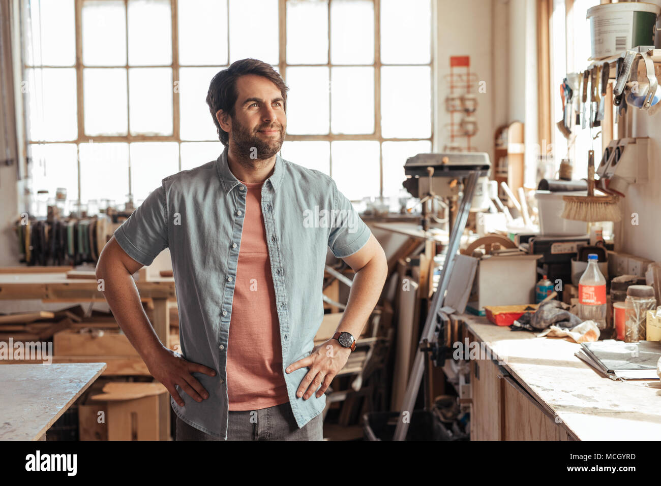 Smiling young woodworker thinking up new designs while standing with his arms crossed by a workbench full of tools in his carpentry workshop - Stock Image