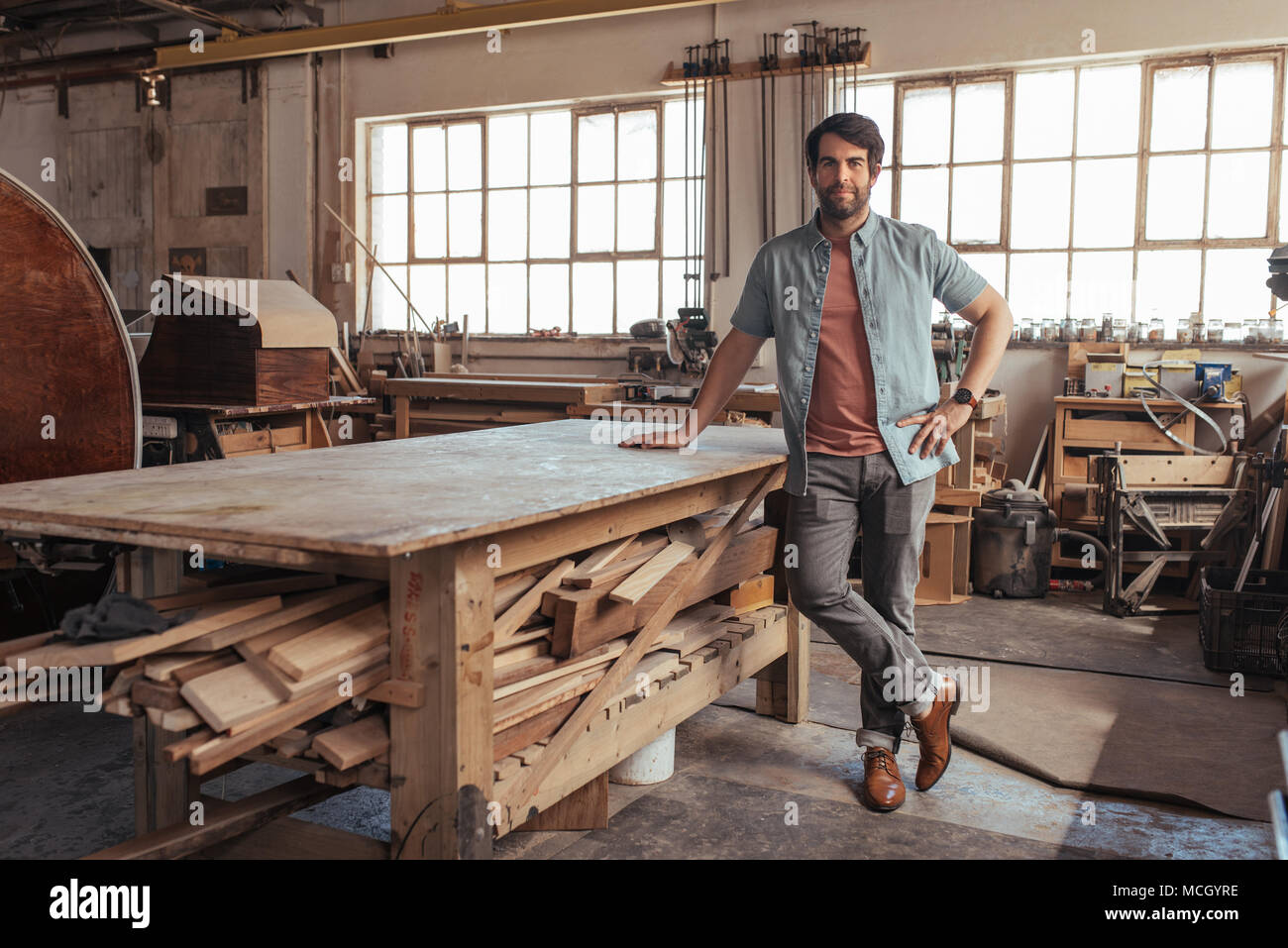 Portrait of a confident young woodworker standing next to a workbench full of wood in his carpentry workshop - Stock Image