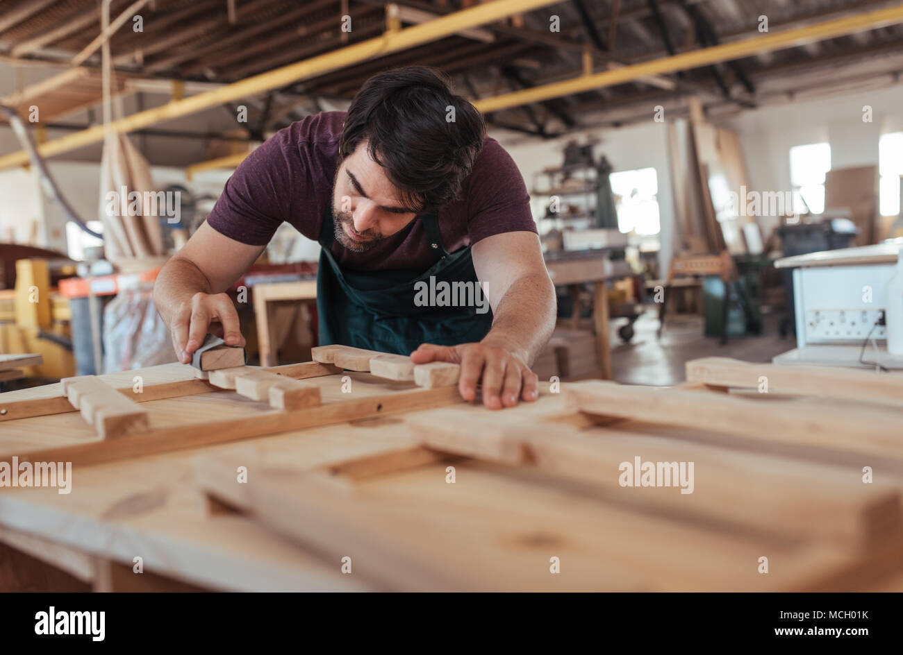 Skilled Young Carpenter With A Beard Hand Sanding Pieces Of A Wooden