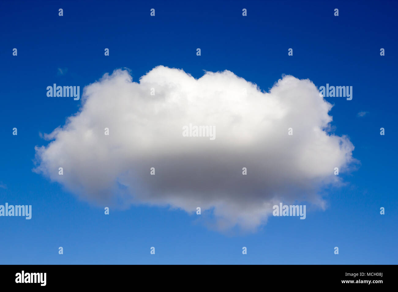 Single fluffy cloud against blue sky - Stock Image