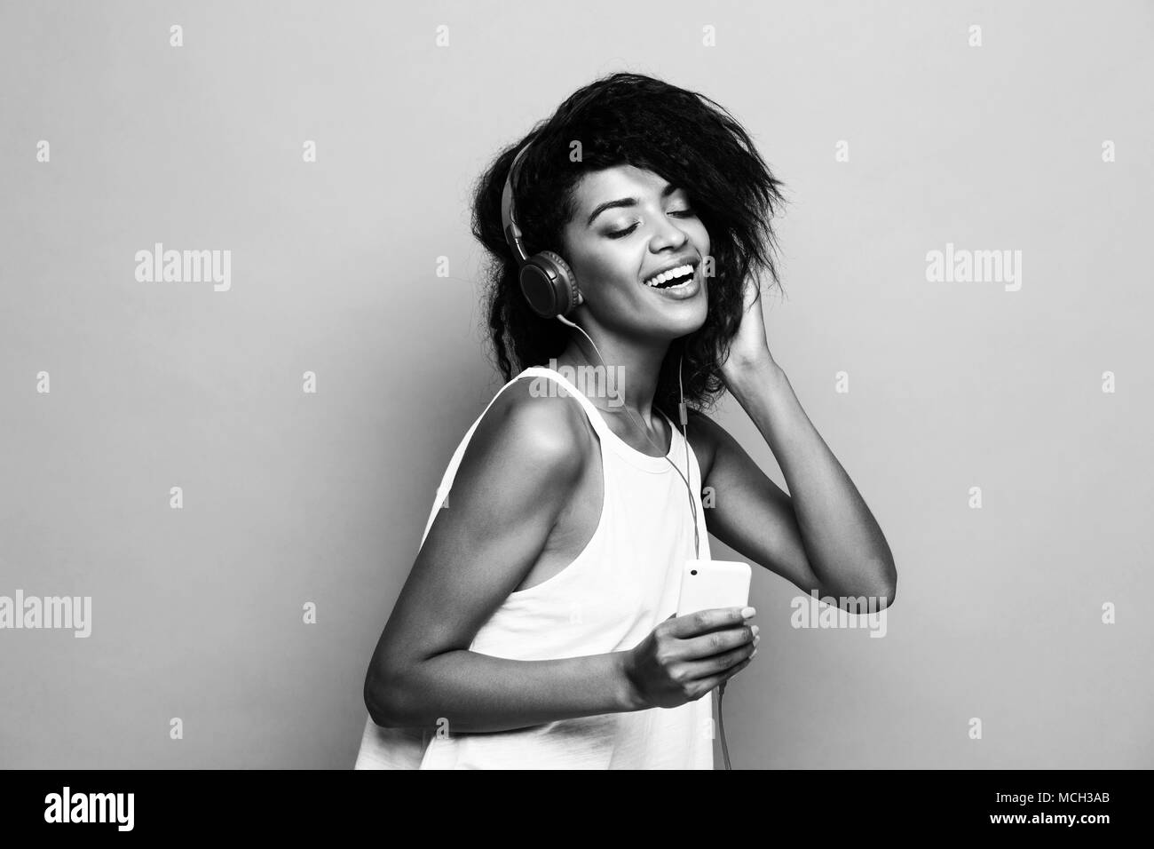 Lifestyle concept portrait of beautiful african american woman joyful listening to music on mobile phone yellow pastel studio background black and white