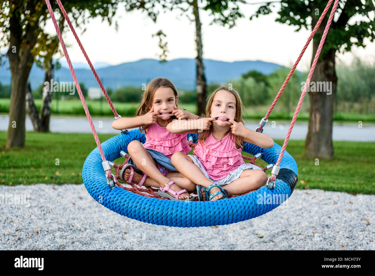 Identical twin girls on spider web nest swing on playground. Active Children playing with Giant Swing-N-Slide Monster Web Swing on outdoors playground Stock Photo