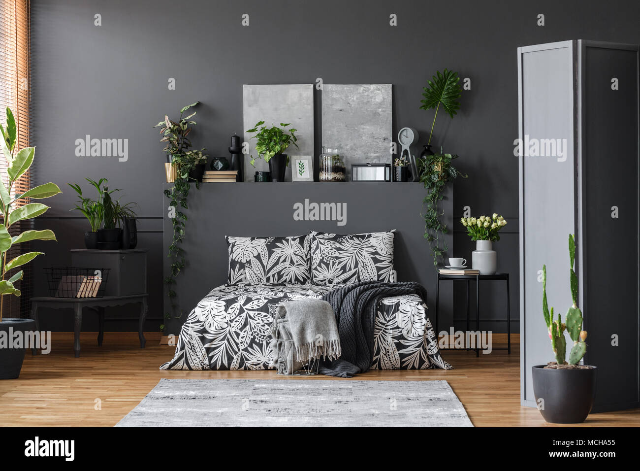 Grey Blanket On Patterned Bed In Floral Bedroom Interior With Plants On  Shelf And Paintings