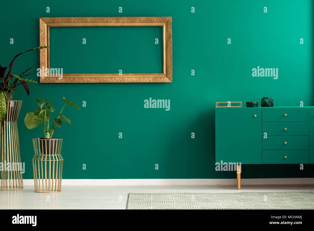 Plant Against The Wall With Empty Gold Frame In Simple Living Room Interior Green Cupboard