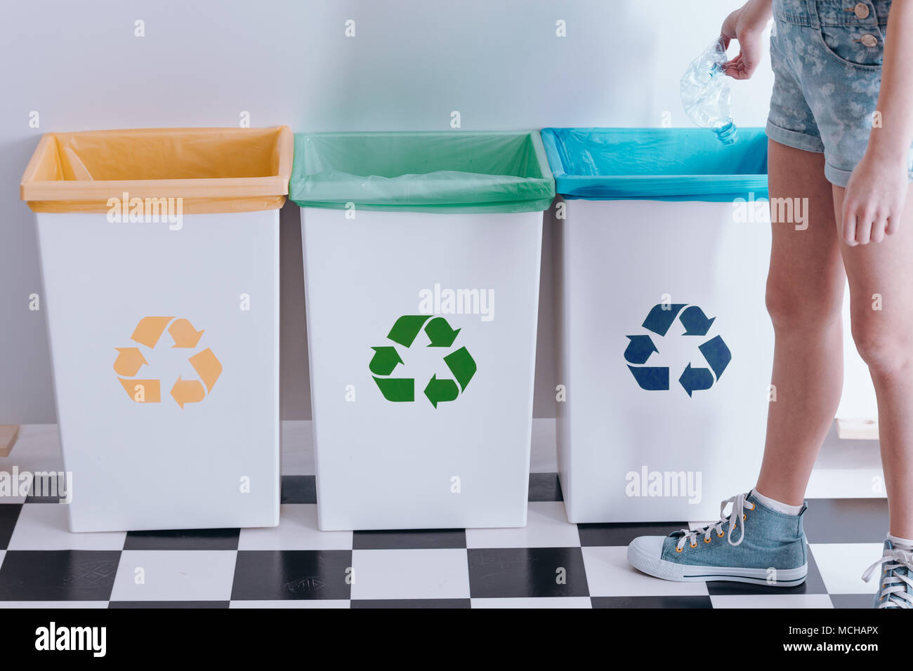 Kid throwing out a plastic bottle into a blue bin. Child recycling education concept - Stock Image