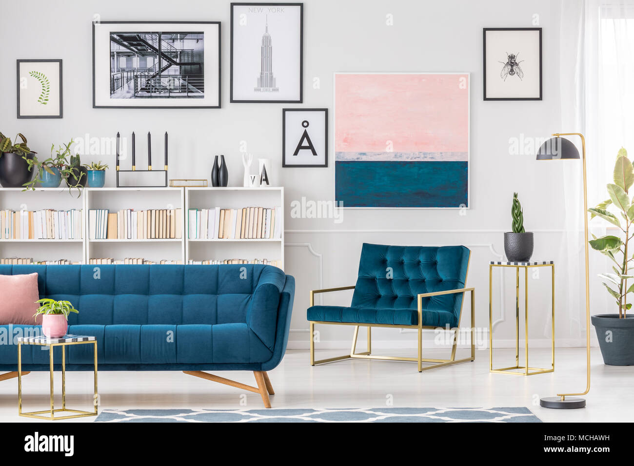 Artistic living room interior with blue sofa and armchair, paintings ...