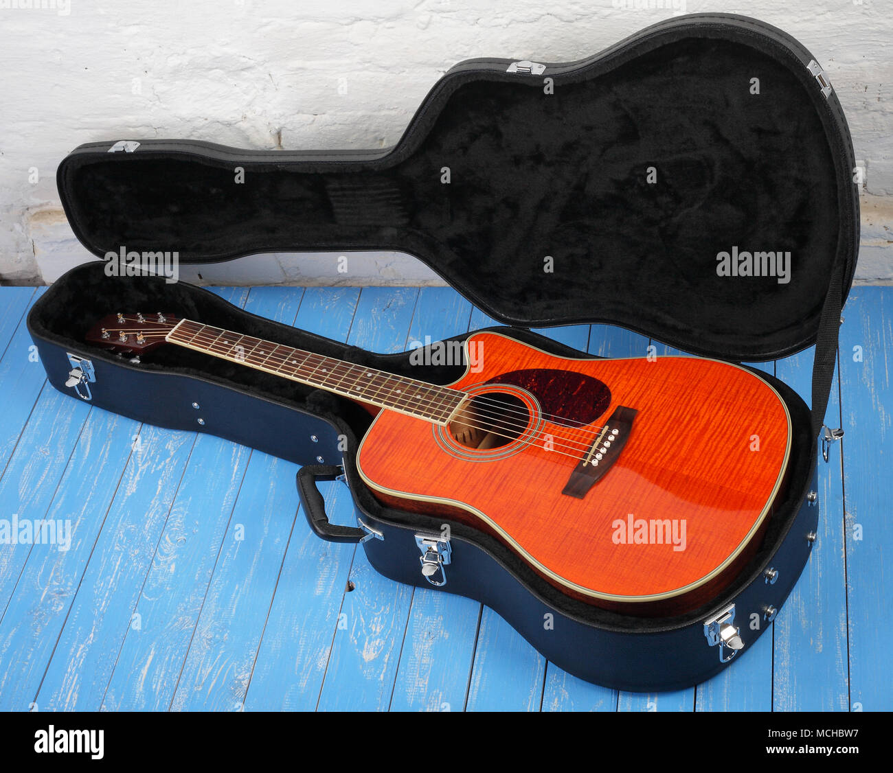 Musical instrument - Orange acoustic guitar in hard case on a blue wood, and white brock wall background. Stock Photo