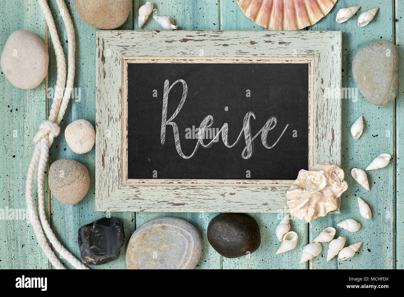 """Blackboard With Maritime Decorations on light wood, text in German. """"Reise"""" means """"Vacations"""". Stock Photo"""