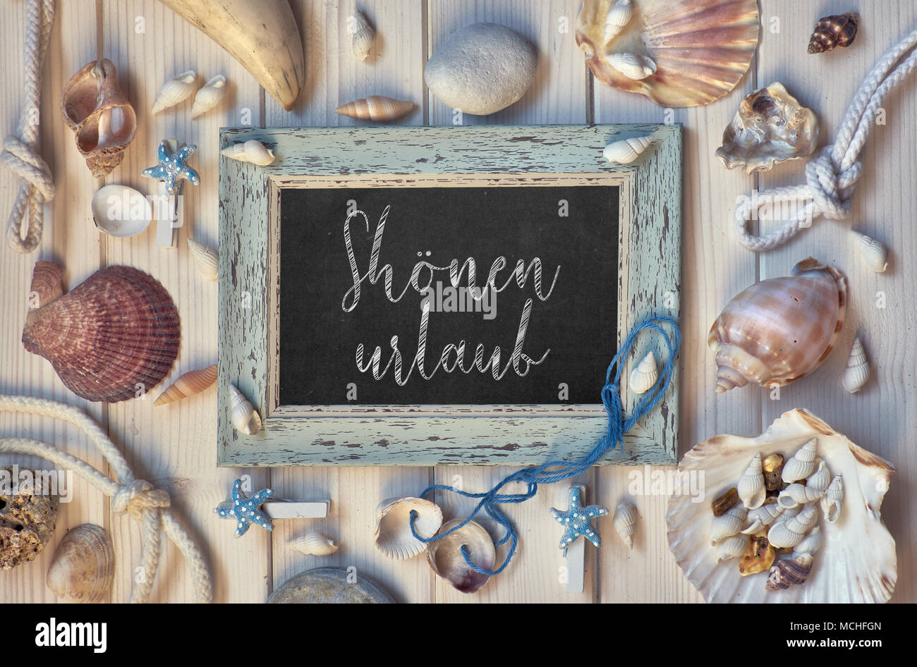 Blackboard With Maritime Decorations on light wood, text in German, 'Shonen urlaub' Means 'Happy holidays' - Stock Image