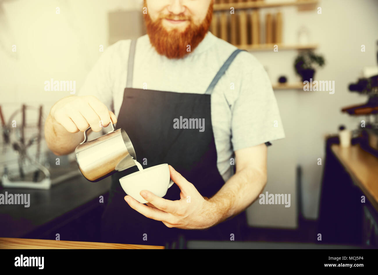 Coffee Business Concept - handsome bearded man in apron making coffee while standing at cafe - Stock Image