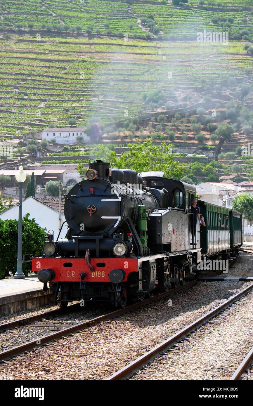 Douro Historical Steam Train approaching Pinhão Railway Station, Pinhão, Alto Douro Wine Region, Portugal - Stock Image