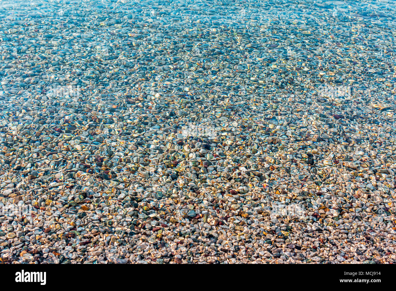 Background Of Blurred Bright Colorful Sea Stones Under Water Iridescent Sunlight On The Transparent Clear
