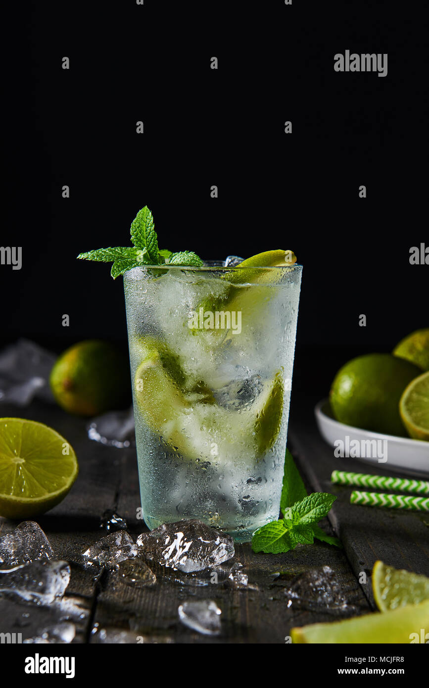 Mojito cocktail with lime and mint in highball glass with ice on a dark wood background with copy space at the top. Stock Photo