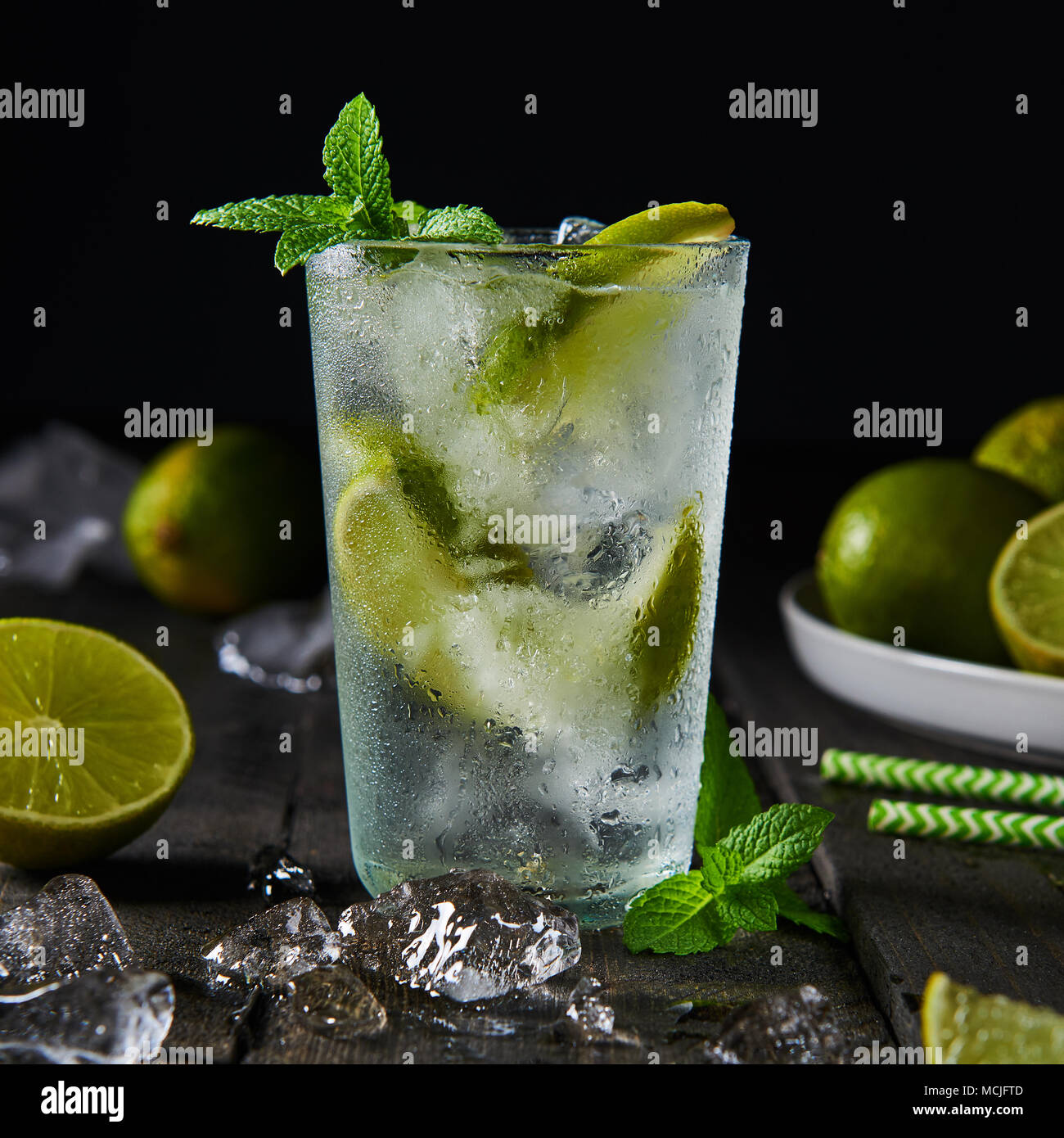 Mojito cocktail with lime and mint in highball glass with ice on a dark wood background. Square crop. - Stock Image
