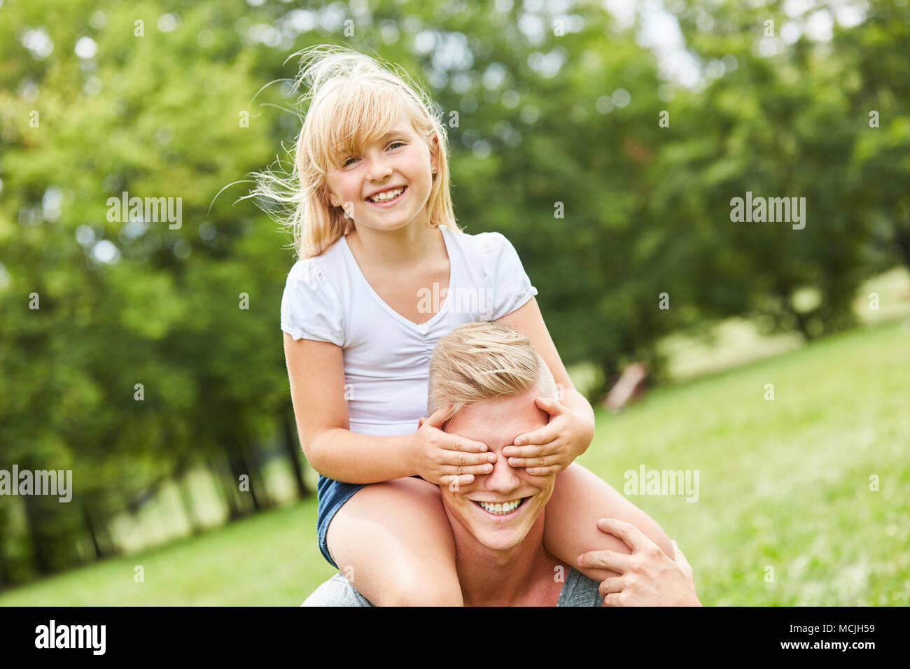 Blond girl sits piggy back on father and keeps his eyes closed - Stock Image