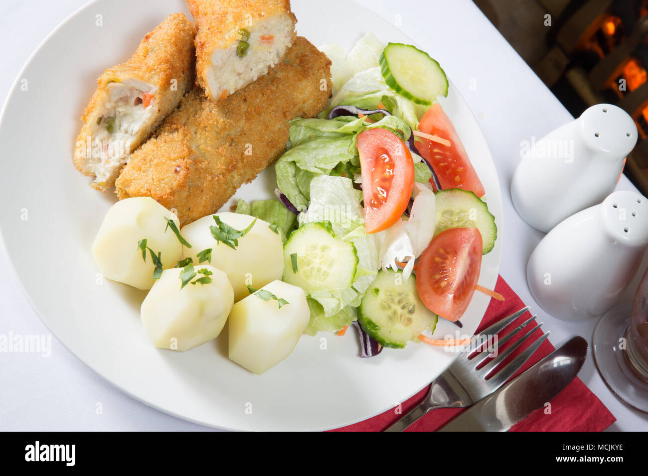 An English pub meal of deep fried breaded Chicken and vegetable rissoles with boiled potatoes and mixed salad - Stock Image