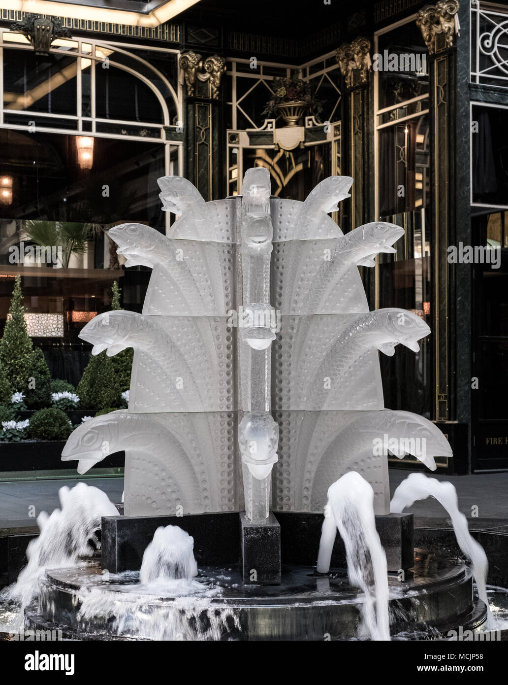 Close up of glass fountain with fish, located outside The Savoy Hotel, off The Strand, London, UK. Fountain designed by French glassmaker Lalique. - Stock Image