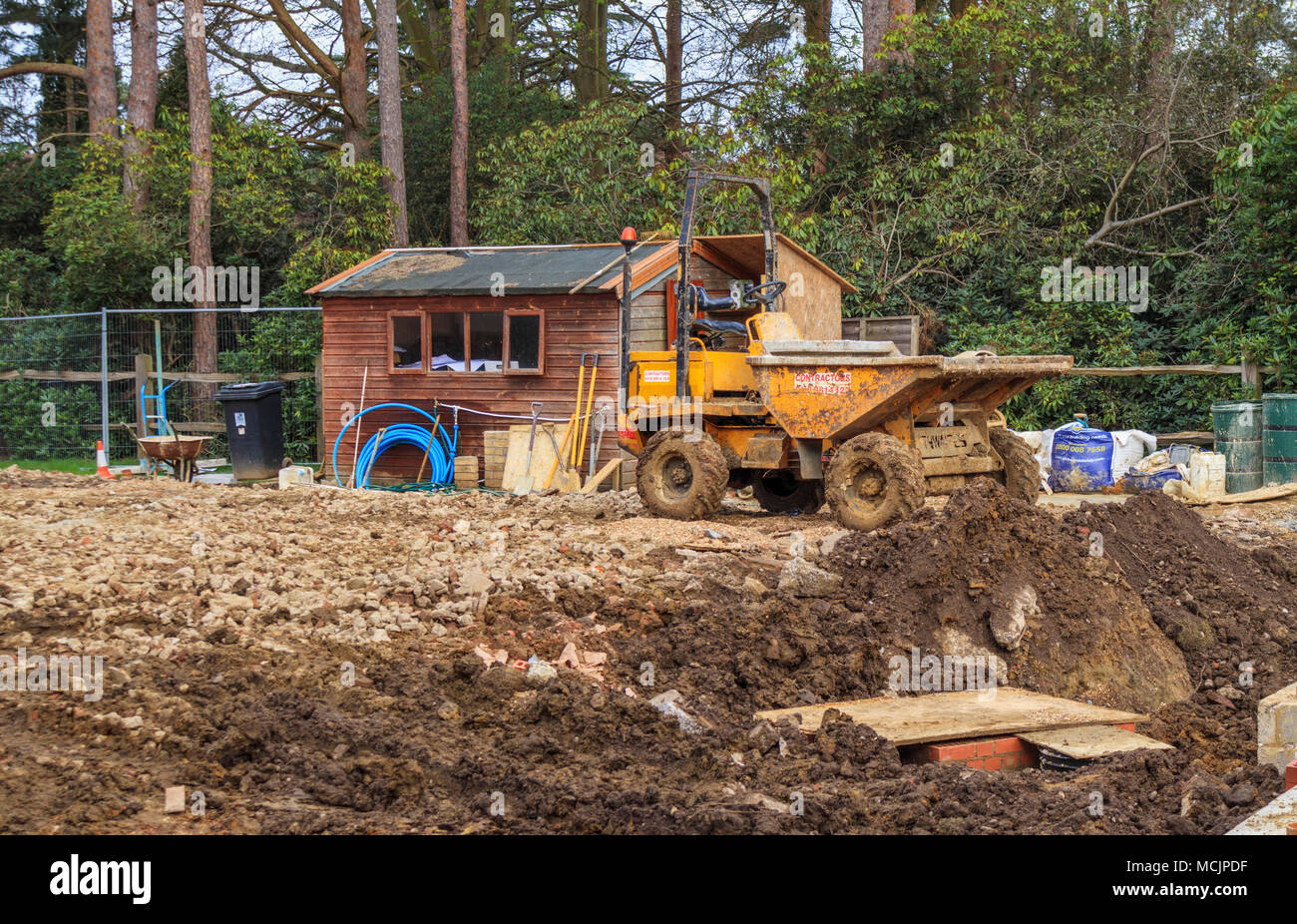 Dumper vehicle on a muddy churned up residential construction site in Surrey, southeast England after wet, bad weather - Stock Image